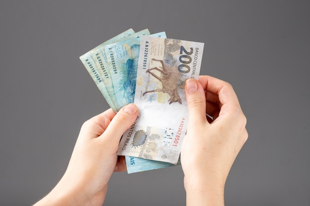 Mão de uma mulher segurando notas de dinheiro brasileiro