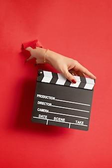 Mão de uma mulher segurando o badalo do filme através do buraco na parede de papel vermelho. claquete de produção de filmes, vlog, conceito de filme