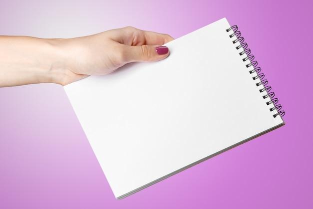 Mão de uma mulher segurando o bloco de notas em branco em espiral.