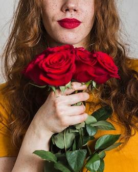 Mão de uma mulher segurando o buquê de rosas