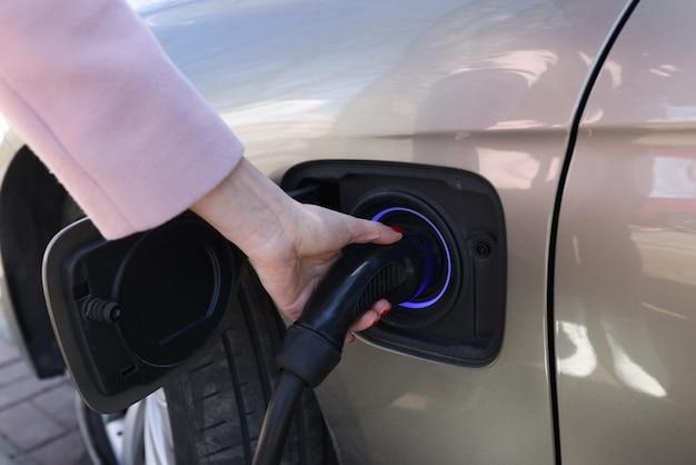 Mão de uma mulher segurando o carregador para carro, close-up