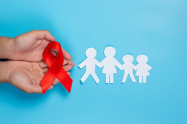 Mão de uma mulher segurando o conceito de conscientização de hiv fita vermelha dia mundial da aids e dia mundial da saúde sexual.