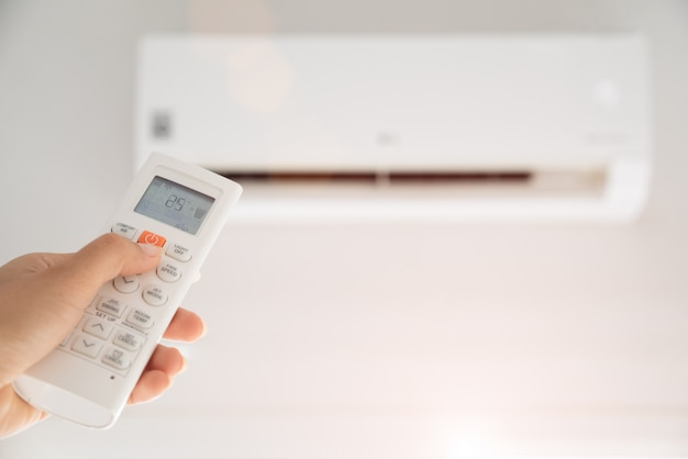 Mão de uma mulher segurando o controle remoto dirigido sobre o ar condicionado dentro da sala