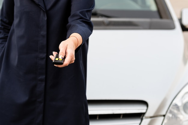 Mão de uma mulher segurando o controle remoto do carro, ele pressiona o controle remoto para abrir a porta do carro