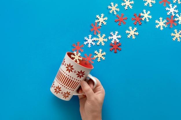 Mão de uma mulher segurando o copo com decorações sazonais vermelhas e brancas com uma trilha de flocos de neve vindo em sua direção. vista plana leiga, superior na parede de papel azul pastel.