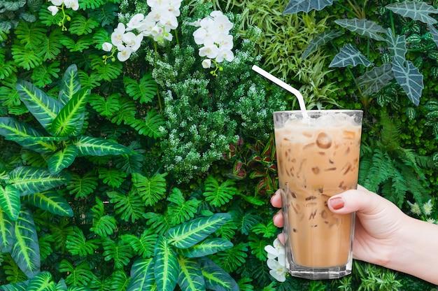 Mão de uma mulher segurando o copo de café gelado sobre fundo verde da natureza, café com leite gelado