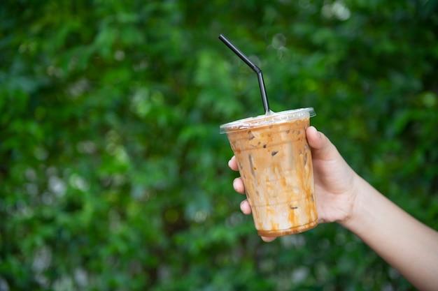 Mão de uma mulher segurando o copo de café gelado