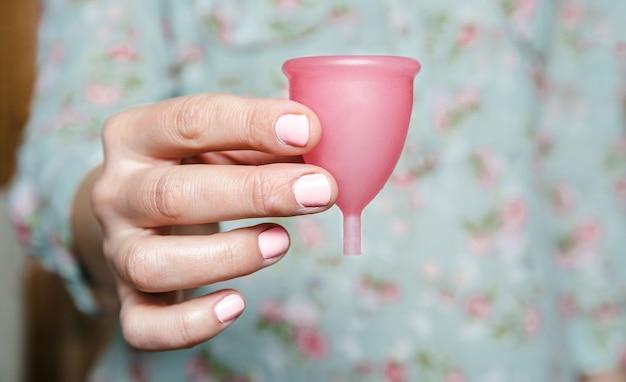 Mão de uma mulher segurando o copo menstrual rosa. conceito moderno de higiene íntima feminina.