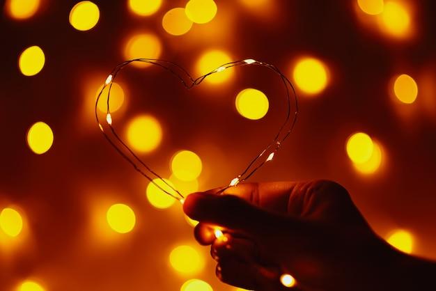 Mão de uma mulher segurando o fio em forma de coração contra abstrato com luzes desfocadas douradas. conceito de dia dos namorados