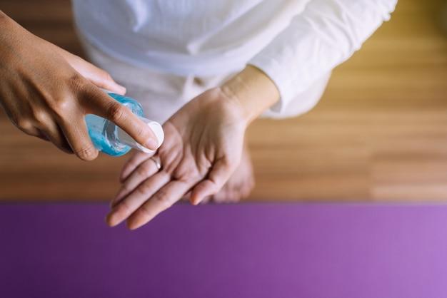 Mão de uma mulher segurando o frasco de gel desinfetante para proteção de coronavírus de higiene de mãos no quarto
