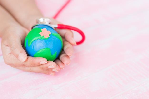 Mão de uma mulher segurando o globo artesanal com estetoscópio vermelho sobre fundo rosa de madeira