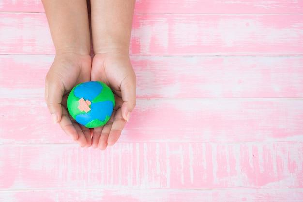 Mão de uma mulher segurando o globo artesanal no fundo da mesa de madeira