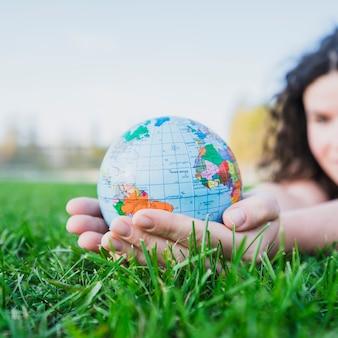 Mão de uma mulher segurando o globo sobre a relva verde