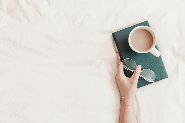 Mão de uma mulher segurando o livro com óculos e bebida quente nele