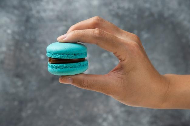 Mão de uma mulher segurando o macaron saboroso azul na superfície de mármore.