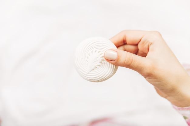Mão de uma mulher segurando o merengue. foto mínima. copie o espaço.
