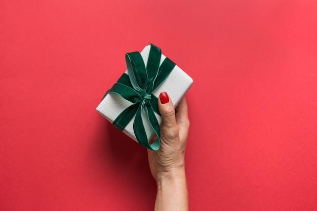 Mão de uma mulher segurando o presente de natal artesanal