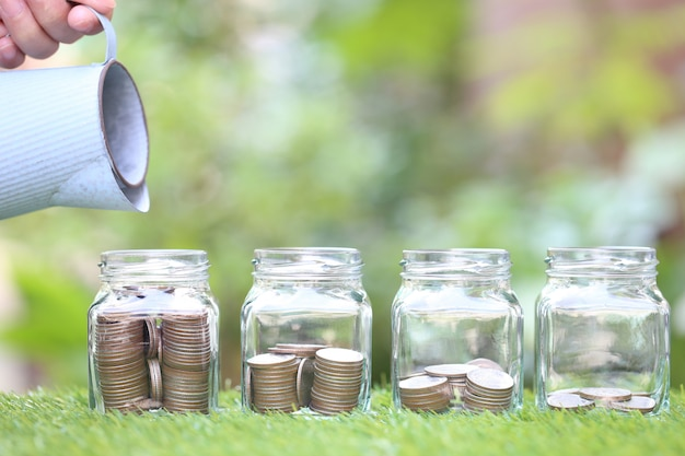 Mão de uma mulher segurando o regador e a pilha de dinheiro moedas em frasco de vidro