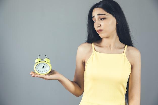 Mão de uma mulher segurando o relógio cinza