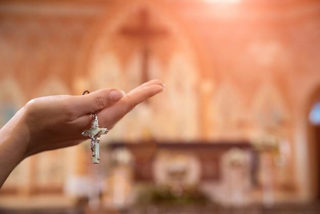Mão de uma mulher segurando o rosário contra a cruz e orando a deus na igreja