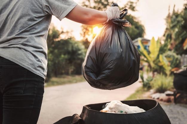 Mão de uma mulher segurando o saco de lixo para limpeza de reciclagem