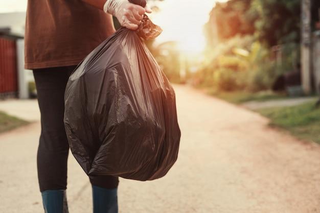 Mão de uma mulher segurando o saco de lixo para reciclar colocando no lixo