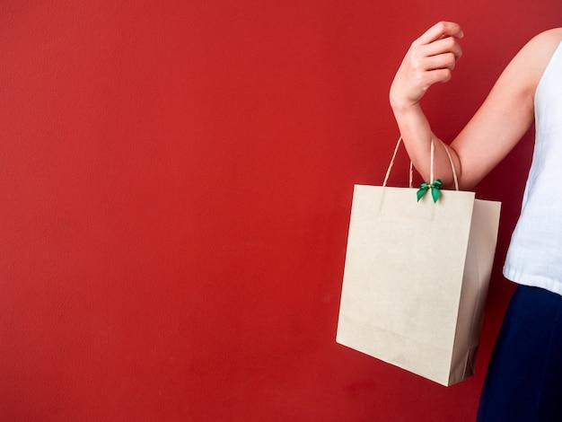 Mão de uma mulher segurando o saco de papel reciclado em branco decorar com laço verde na parede vermelha