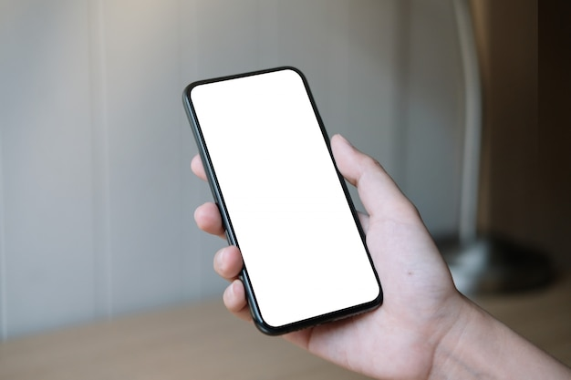 Mão de uma mulher segurando o smartphone com tela branca em branco