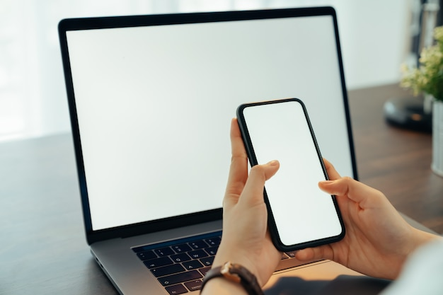Mão de uma mulher segurando o smartphone com tela em branco cópia espaço para seu anúncio. laptop em cima da mesa.