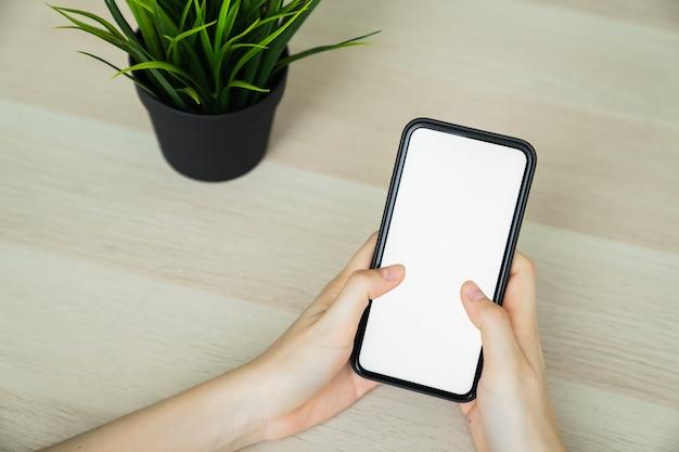 Mão de uma mulher segurando o smartphone e tocando a tela em branco. maquete de propaganda.