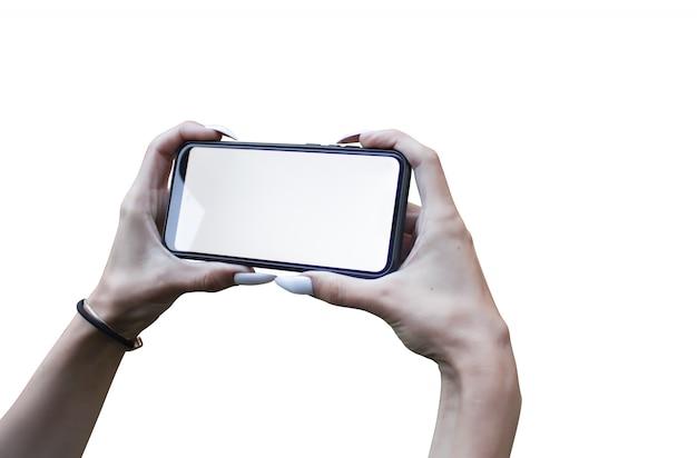 Mão de uma mulher segurando o smartphone mockup preto com tela isolada e lindas unhas.