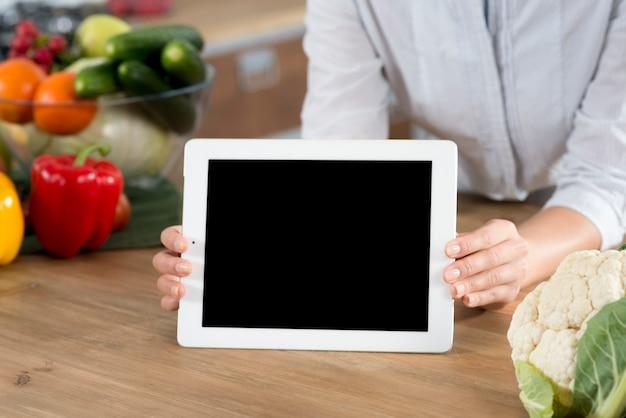 Mão de uma mulher segurando o tablet digital com tela em branco no balcão da cozinha de madeira