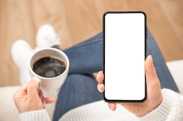Mão de uma mulher segurando o telefone celular branco com a tela da área de trabalho em branco e a xícara de café.