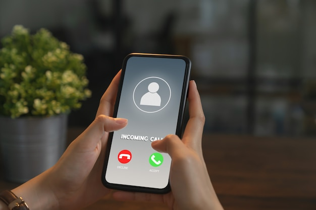Mão de uma mulher segurando o telefone e mostrar a chamada de tela.