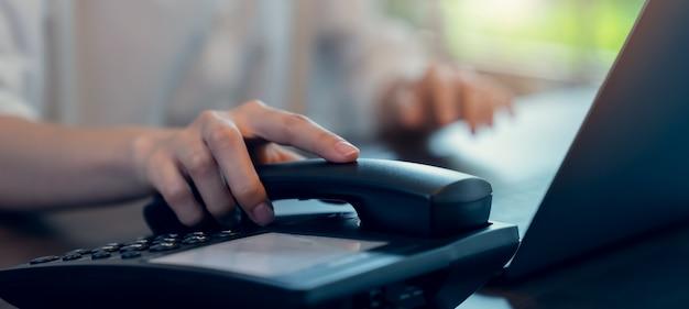 Mão de uma mulher segurando o telefone e trabalhando laptop na mesa de escritório.