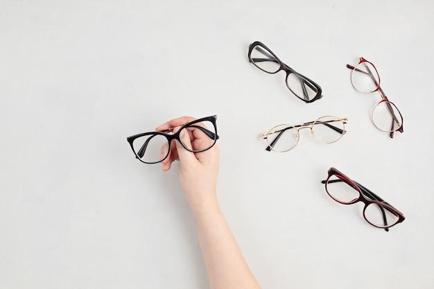 Mão de uma mulher segurando óculos. loja de ótica, seleção de óculos, exame de vista, exame de visão no oculista, conceito de acessórios de moda. vista superior, configuração plana