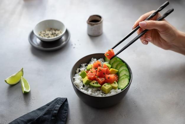 Mão de uma mulher segurando os pauzinhos com uma fatia de salmão e comendo uma tigela de puxão havaiano. comida rápida e saudável, almoço, conceito de nutrição.
