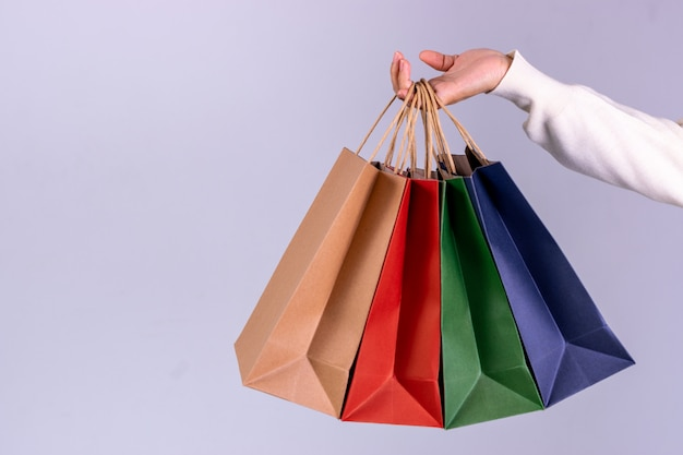 Mão de uma mulher segurando os sacos de papel com espaço de cópia. conceito de black friday ou cyber monday.