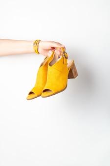 Mão de uma mulher segurando os sapatos femininos amarelos.
