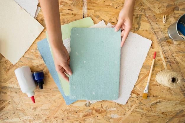 Mão de uma mulher segurando papel artesanal sobre a mesa de madeira