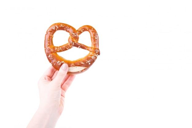 Mão de uma mulher segurando pretzel