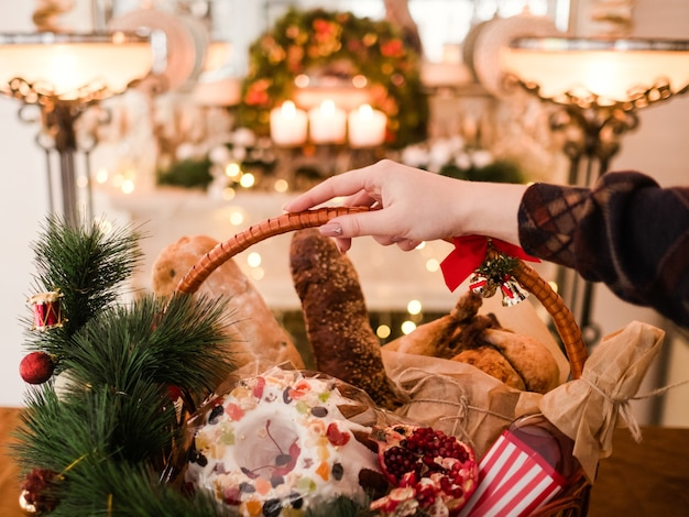 Mão de uma mulher segurando produtos de natal em uma cesta. conceito de presente de comida festiva de feriado