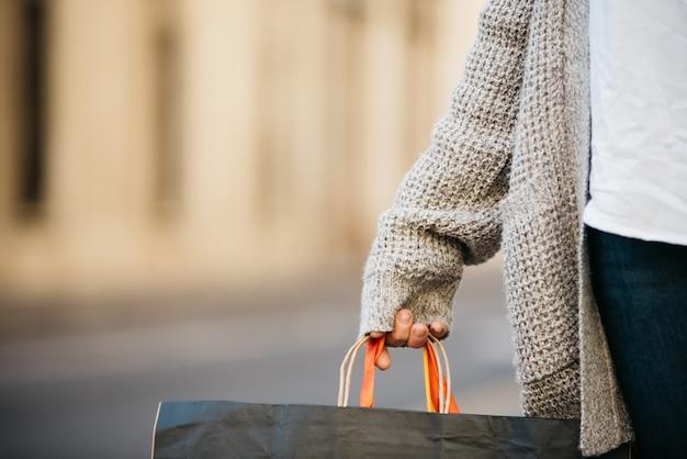 Mão de uma mulher segurando sacolas de compras, com roupas da moda.