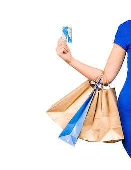 Mão de uma mulher segurando sacolas de compras e cartão de crédito em fundo branco isolado