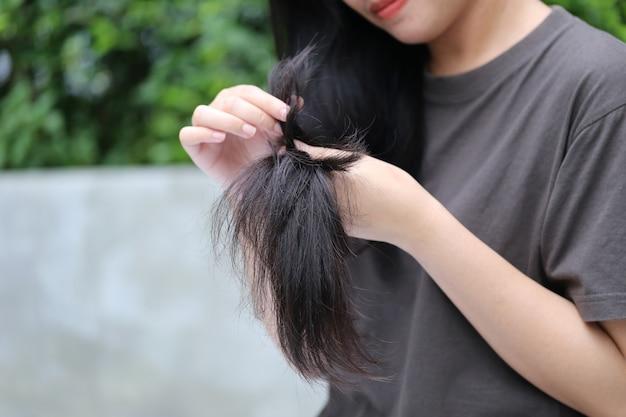 Mão de uma mulher segurando seu cabelo comprido olhando para pontas danificadas e rachadas de problemas de cuidados com os cabelos
