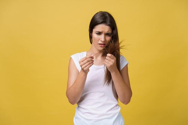 Mão de uma mulher segurando seus longos cabelos com olhar para danificado splitting termina