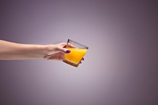 Mão de uma mulher segurando suco de laranja