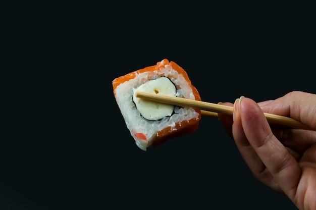 Mão de uma mulher segurando sushi com close-up de palitos de madeira