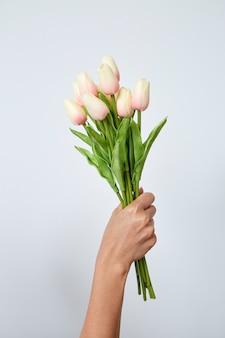 Mão de uma mulher segurando tulipas