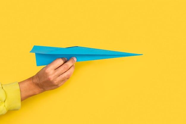 Mão de uma mulher segurando um avião de papel azul